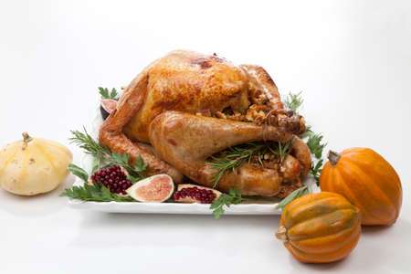 Garnished traditional roasted turkey for Thanksgiving, garnished with fresh figs, pomegranate, and herbs. Stock Photo