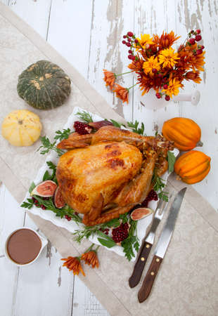 Garnished traditional roasted turkey for Thanksgiving, garnished with fresh figs, pomegranate, and herbs. Pumpkins, fall flowers, and decorations.