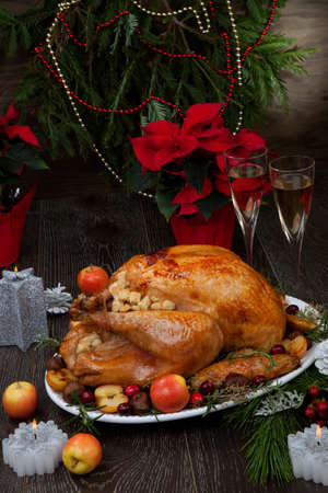 Garnished roasted Christmas turkey with grab apples, sweet chestnut, cranberry, Christmas ornaments, candles, and pine cones.