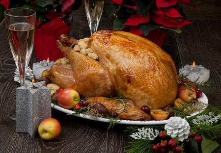 Przyozdobiony pieczony świąteczny indyk z jabłkami, kasztanami, żurawiną, ozdobami świątecznymi, świecami i szyszkami.