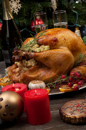 Rustic style roasted Christmas turkey garnished with roasted garlic, lemon, and rosehips. Surrounded with rustic Christmas ornaments, candles, wine, flowers, and Christmas tree in the background. Banco de Imagens