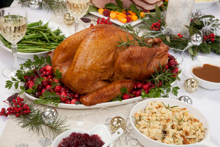 Smoked turkey on a tray garnished with fresh cranberries and herbs for Christmas celebration.