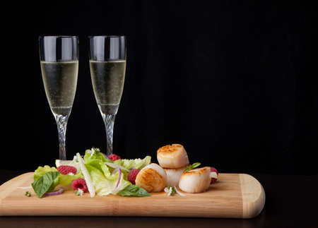 Close up of delicious savory fried scallops salad with Glass of Champagne.