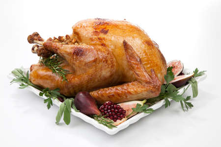 Garnished traditional roasted turkey, garnished with fresh figs, pomegranate, and herbs.