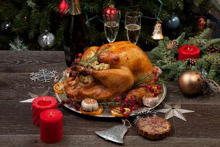 Rustic style roasted Christmas turkey garnished with roasted garlic, lemon, and rosehips.