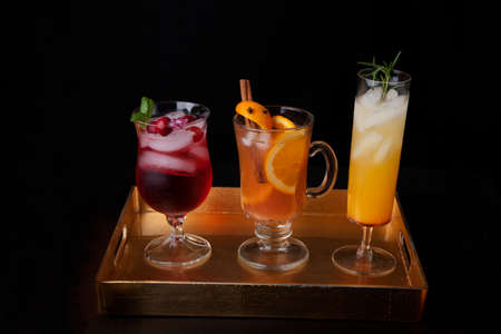Closeup of Spicy Apple Cider, Pear Sparkler, and Whiskey-Cranberry cocktails on a tray with mini pumpkins. Fall Drinks series. Stock Photo