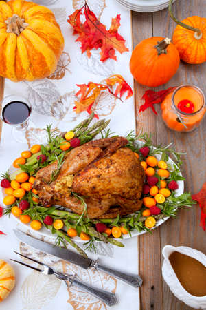 Citrus glazed roasted Turkey for Thankgiving celebration garnished with kumquat, raspberry, asparagus, oregano, and fresh rosemary twigs. Red wine, side dishes, and gravy. Holiday table decoraded with pumpkins, candels, gourds, and fall leaves.