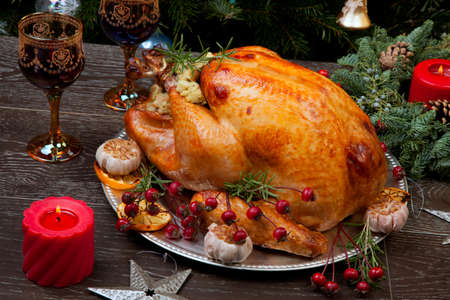 Rustic style roasted Christmas turkey garnished with roasted garlic, lemon, and rosehips. Surrounded with rustic Christmas ornaments, candles, wine, flowers, and Christmas tree in the background. Standard-Bild