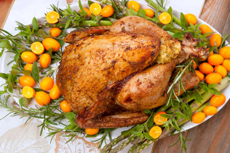 Citrus glazed roasted Turkey for Thanksgiving celebration garnished with kumquat, raspberry, asparagus, oregano, and fresh rosemary twigs. Red wine, side dishes, and gravy. Reklamní fotografie