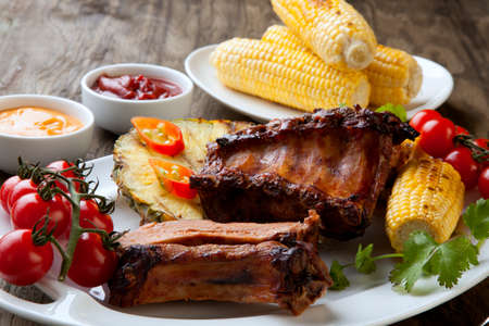 Grilled pork ribs, corn, and pineapple with chili pepper, cherry tomatoes, and sauces. Reklamní fotografie