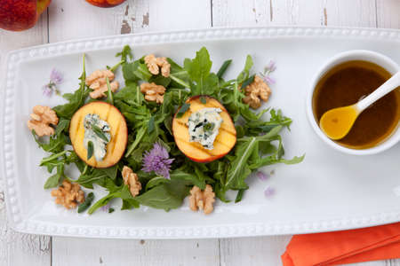 Closeup of blue cheese and peach salad with walnut and arugula. Freash peaches. Reklamní fotografie