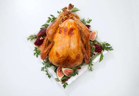 Garnished traditional roasted turkey, garnished with fresh figs, pomegranate, and herbs. On white background. Reklamní fotografie