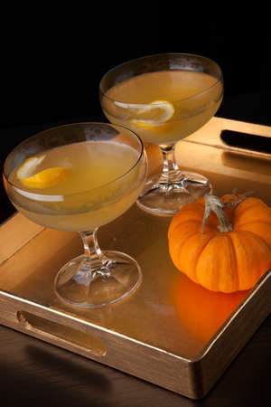 Closeup of Champagne Cocktail on a tray with mini pumpkins. Fall Drinks series.