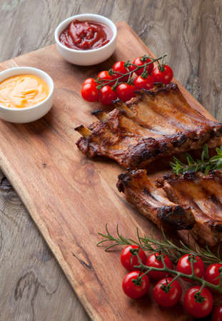 Grilled pork ribs with fresh cherry tomatoes, rosemary, oregano served with ketchup and mustard sauce on wooden board.