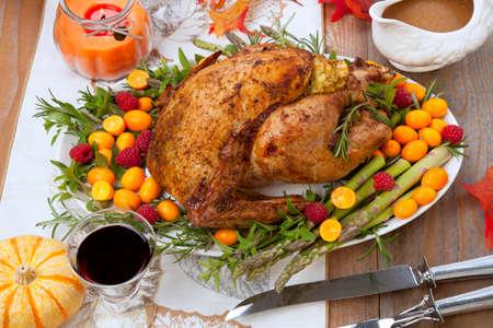 Citrus glazed roasted Turkey for Thanksgiving celebration garnished with kumquat, raspberry, asparagus, oregano, and fresh rosemary twigs. Red wine, side dishes, and gravy. Standard-Bild