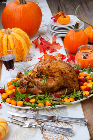 Citrus glazed roasted Turkey for Thanksgiving celebration garnished with kumquat, raspberry, asparagus, oregano, and fresh rosemary twigs. Red wine, side dishes, and gravy. Holiday table decorated with pumpkins, candles, gourds, and fall leaves.