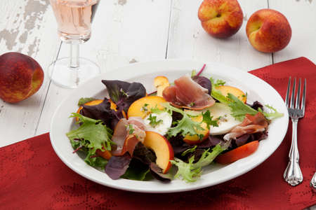 Closeup of Prosciutto peach salad with fresh Mozzarella plate mixed with spring greens. Fresh peaches.