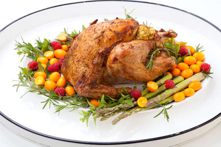 citrus glazed roasted Turkey on white tray for Thanksgiving celebration garnished with kumquat, raspberry, asparagus, oregano, and fresh rosemary twigs. Mini pumpkins. Reklamní fotografie