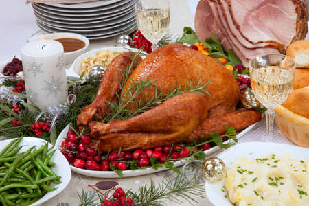 Smoked turkey on a tray garnished with fresh cranberries and herbs, roasted ham, side dishes, decoration and ornamets for Christmas celebration. Reklamní fotografie