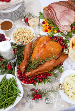 Smoked turkey on a tray garnished with fresh cranberries and herbs, roasted ham, side dishes, decoration and ornamets for Christmas celebration. Standard-Bild
