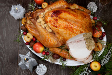 Carving garnished roasted Christmas turkey with grab apples, sweet chestnut, cranberry, Christmas ornaments, candles, and pine cones. Stockfoto