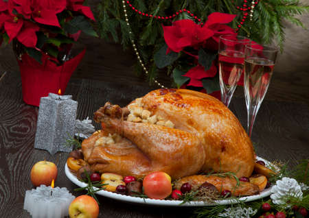 Garnished roasted Christmas turkey with grab apples, sweet chestnut, cranberry, Christmas ornaments, candles, and pine cones. Stockfoto