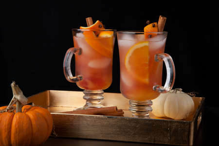 Closeup of Spicy Apple Cider on a tray with mini pumpkins, fresh apples, and cinnamon sticks. Fall Drinks series.