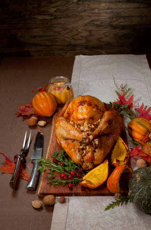 Garnished traditional roasted turkey for Thanksgiving, garnished with roasted winter squash, cranberry, nuts, and fresh herbs. Decoraded with pumpkins, candels, and flowers.