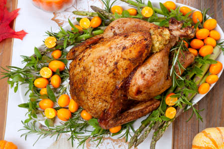 Citrus glazed roasted Turkey for Thanksgiving celebration garnished with kumquat, raspberry, asparagus, oregano, and fresh rosemary twigs. Red wine, side dishes, and gravy. Holiday table decorated with pumpkins, candels, gourds, and fall leaves.
