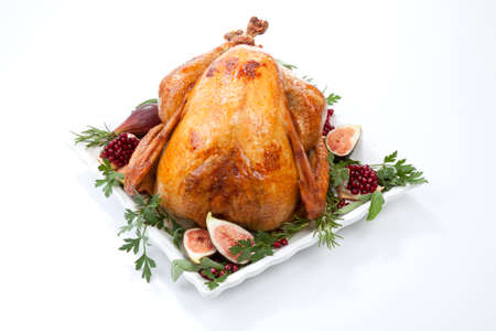 Garnished traditional roasted turkey, garnished with fresh figs, pomegranate, and herbs. On white background. Standard-Bild