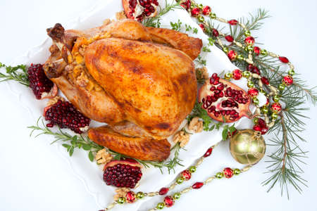 Pomegranate glazed roasted turkey on a tray garnished with fresh pomegranates, herbs, and walnuts over white background. Christmas ornaments and fir twigs. Reklamní fotografie