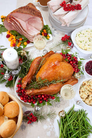 Roasted ham garnished with fresh raspberry, kumquat, and mint. Smocked turkey with cranberries and herbs, side dishes, decoration and ornamets for Christmas celebration.