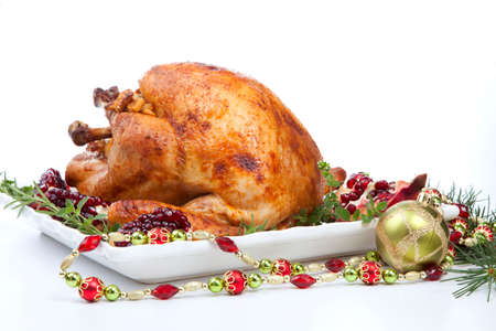 Pomegranate glazed roasted turkey on a tray garnished with fresh pomegranates, herbs, and walnuts over white background. Christmas ornaments and fir twigs. Standard-Bild