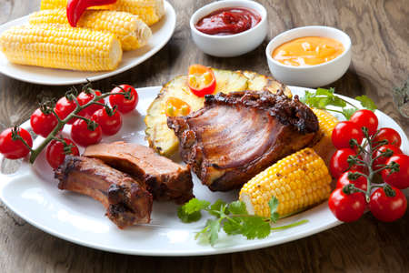 Grilled pork ribs, corn, and pineapple with chili pepper, cherry tomatoes, and sauces. Standard-Bild