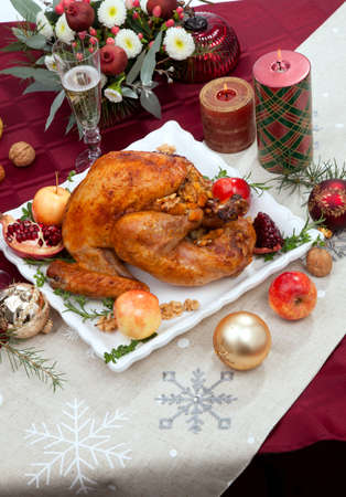 Pomegranate glazed roasted turkey on a tray garnished with fresh pomegranates, apples, herbs, and walnuts on Christmas-decorated table with candles, ornaments, fir twigs and flutes of champagne.