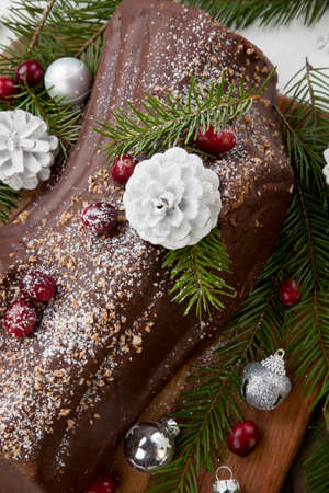 Traditional Christmas chocolate yule log cake with cranberry, Christmas ornamets, and decorations.