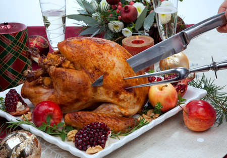 Carving pomegranate glazed roasted turkey on a tray garnished with fresh pomegranates, apples, herbs, and walnuts on Christmas-decorated table with candles, ornaments, fir twigs and flutes of champagne. Standard-Bild