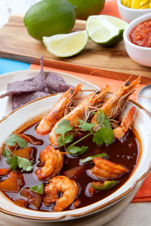 Closeup of a bowl of hot delicious spicy Mexican shrimp soup, garnished with whole shrimps and fresh cilantro. Limes, blue corn chips, salsa, guacamole, and marinated hot pepper.