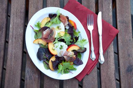 Closeup of Prosciutto peach salad with rresh Mozzarella plate mixed with spring greens. Freash peaches. Standard-Bild
