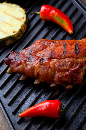 Grilled pork ribs on griddle with chili pepper and grilled pineapple.