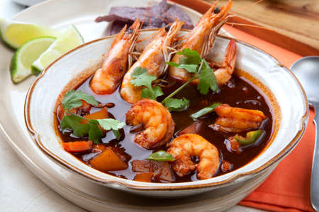 Closeup of a bowl of hot delicious spicy Mexican shrimp soup, garnished with whole shrimps and fresh cilantro.