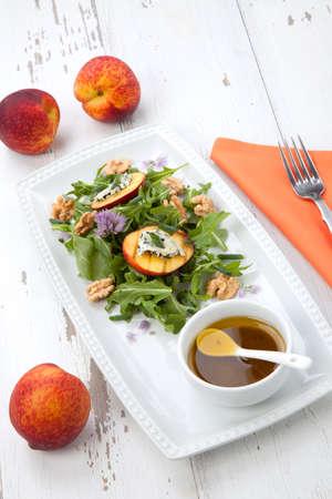 Closeup of blue cheese and peach salad with walnut and arugula. Freash peaches. Standard-Bild