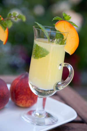 Closeup of Peach Mojito garnished with peach wedge and twig of mint.