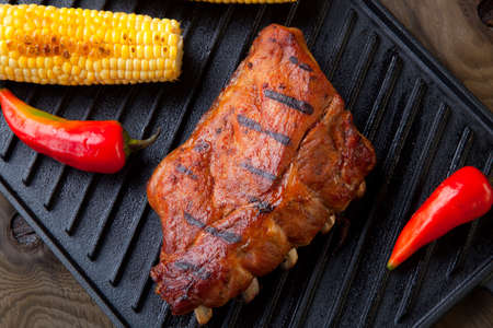 Grilled pork ribs on griddle with chili pepper, cherry tomatoes, and grilled corn