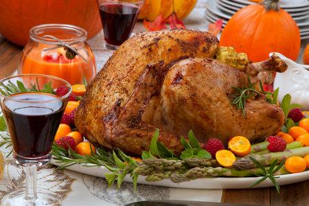 Citrus glazed roasted Turkey for Thanksgiving celebration garnished with kumquat, raspberry, asparagus, oregano, and fresh rosemary twigs.