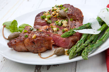 Grilled steak dressed with olive tapenade garnished with asparagus and cheese.