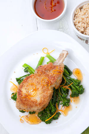 Closeup of sesame-crumbed pork chops with asian greens.