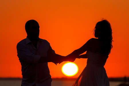 silhouetted: lovers silhouetted against a setting sun on the beach