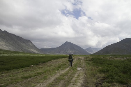 compas: traveler in the highlands with equipment on the road