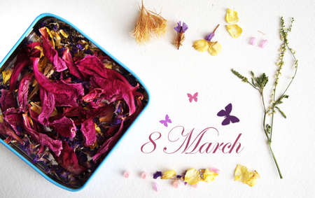 postcard to the international womens day, March 8, from dried flowers and a gift box and butterflies